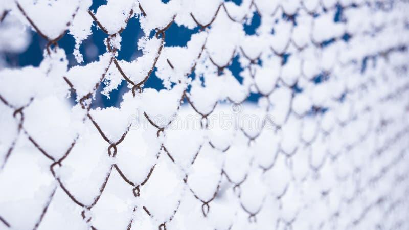 Netomheining in de sneeuw heel wat sneeuw op de ijzeromheining stock foto