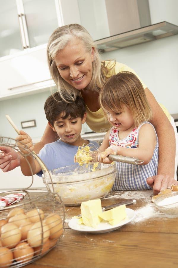 Netos que ajudam a avó a cozer bolos na cozinha imagem de stock