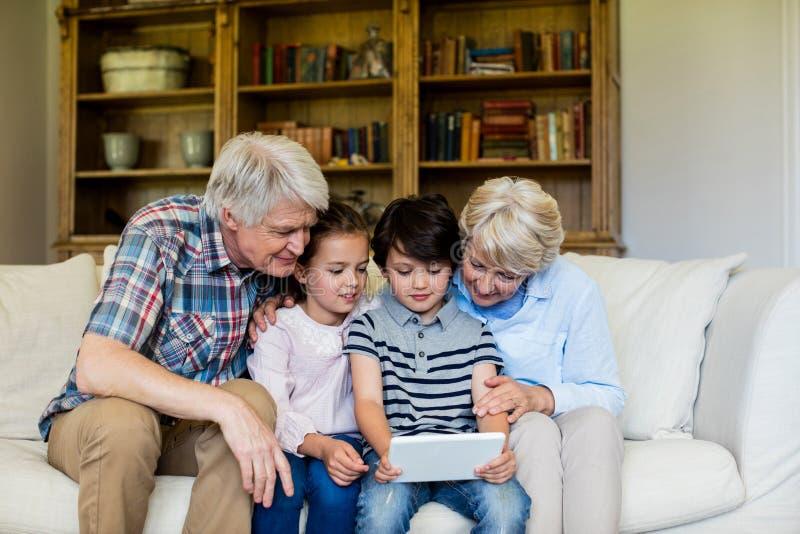 Netos que usam a tabuleta digital com suas avós fotografia de stock royalty free