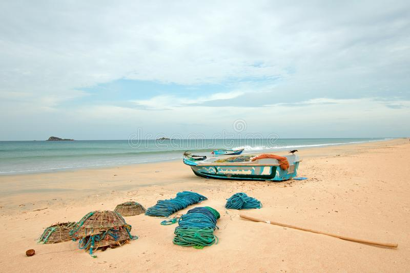 Nets, traps, baskets, and ropes next to fishing boat on Nilaveli beach in Trincomalee Sri Lanka. Asia stock image