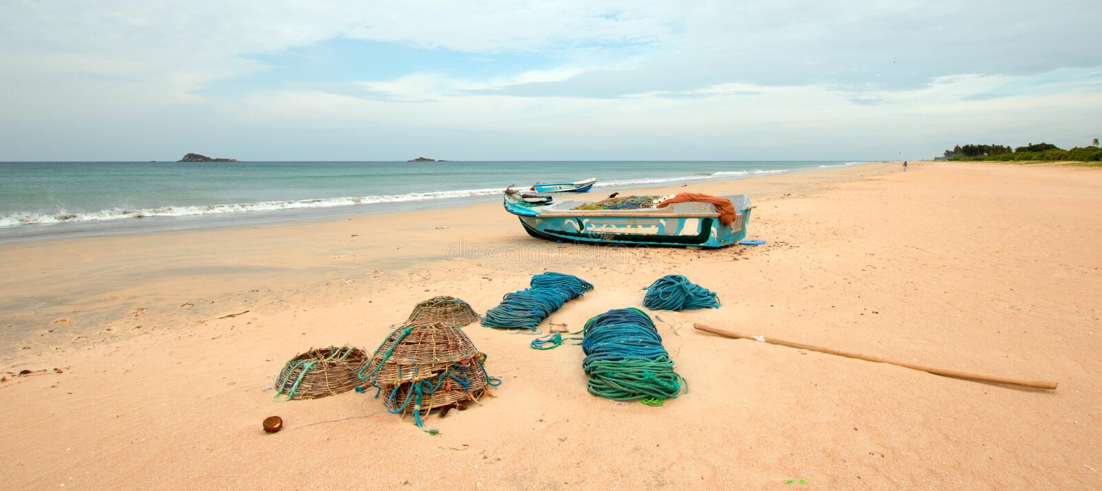 Nets, traps, baskets, and ropes next to fishing boat on Nilaveli beach in Trincomalee Sri Lanka. Asia stock photography