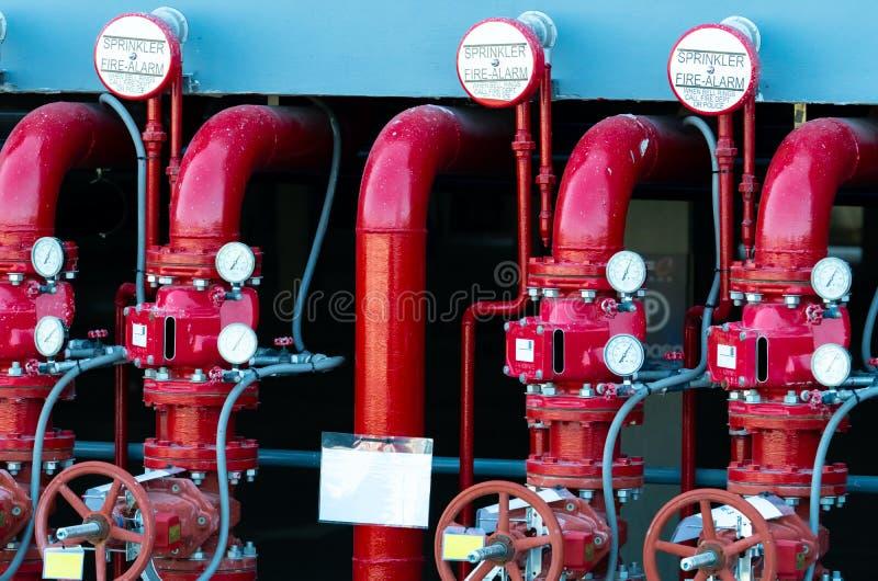 Netstroomwater het door buizen leiden in het brandblussysteem Brandsprenkelinstallatie met rode pijpen Brandafschaffing Handklep stock foto's