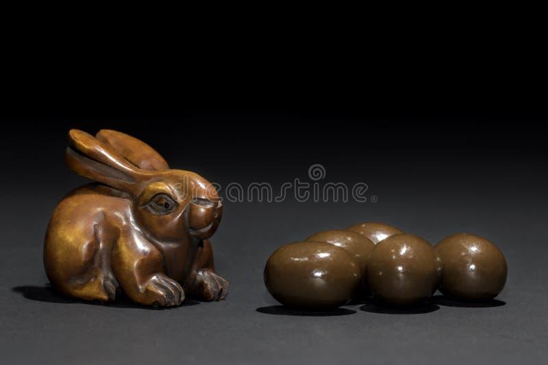 Netsuke de lapin de Pâques avec de mini oeufs de pâques images libres de droits