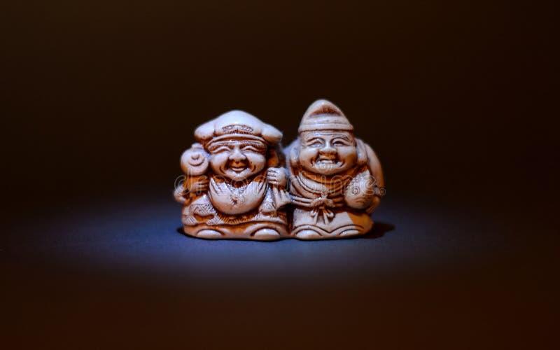 Netsuke miniatura hermoso de un par de pescados en fondo oscuro imagen de archivo libre de regalías