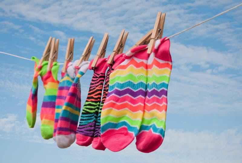 Nett bunte Socken, die auf Wäscheleine trocknen lizenzfreie stockfotos