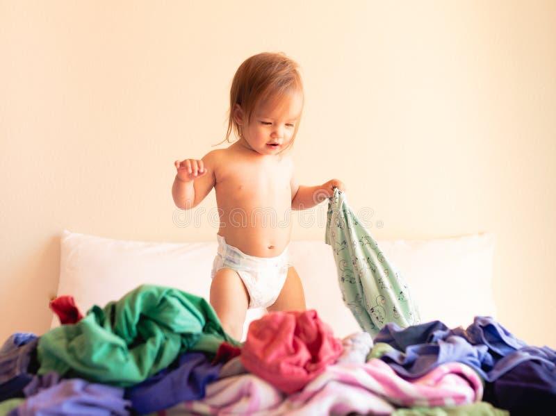 Nett, entz?ckend, l?chelnd, kaukasisches Baby, das in einem Stapel der Schmutzw?sche auf Bett sitzt lizenzfreie stockbilder