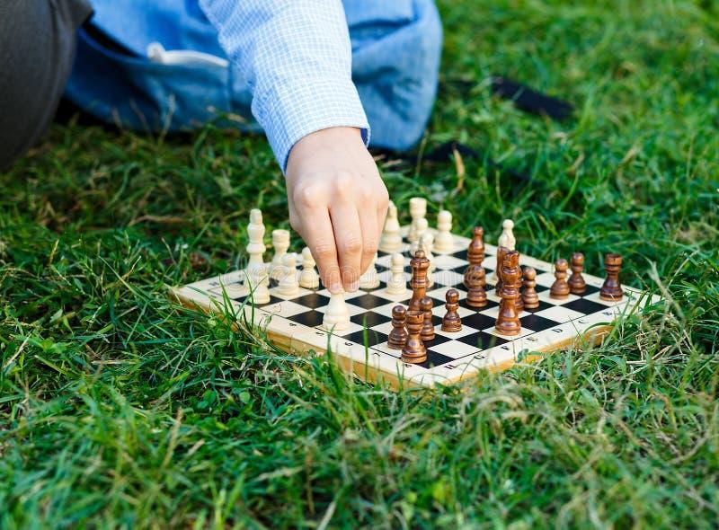 Nett, Junge in den blauen Hemdspielen auf dem hölzernen Schachbrett auf dem Gras im Park Ausbildung, Gedankenspiel lizenzfreies stockbild