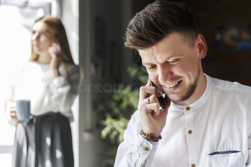 Nett und gut aussehender Mann ist, sprechend sitzend und am Telefon Er ist unten lachend und schauend Mädchen steht außer Fenster lizenzfreie stockfotografie