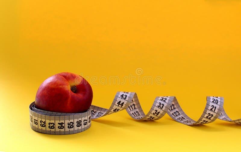 Nettarina di dieta della frutta avvolta in nastro di centimetro immagine stock