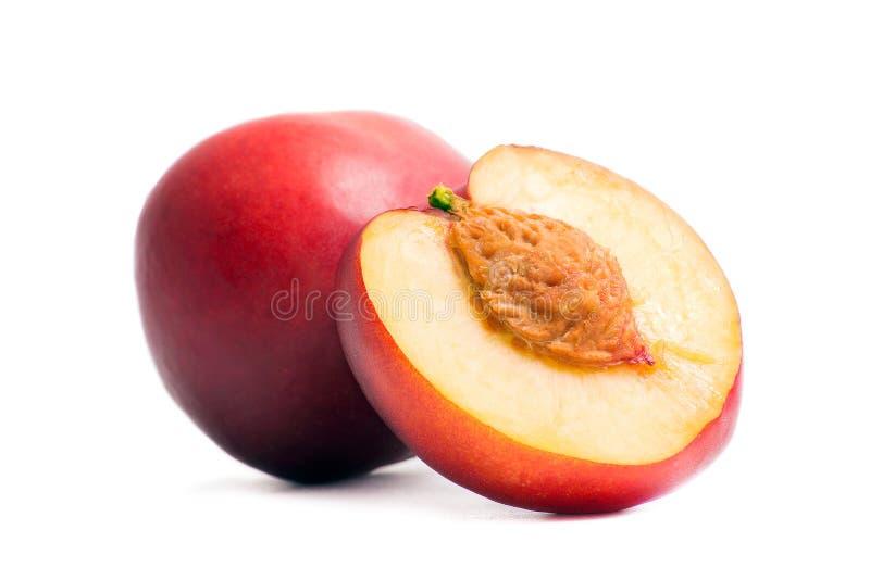 Nettarina intera e metà della nettarina con una pietra Nettarine isolate su un fondo bianco Frutta succosa di estate Alimento san immagini stock