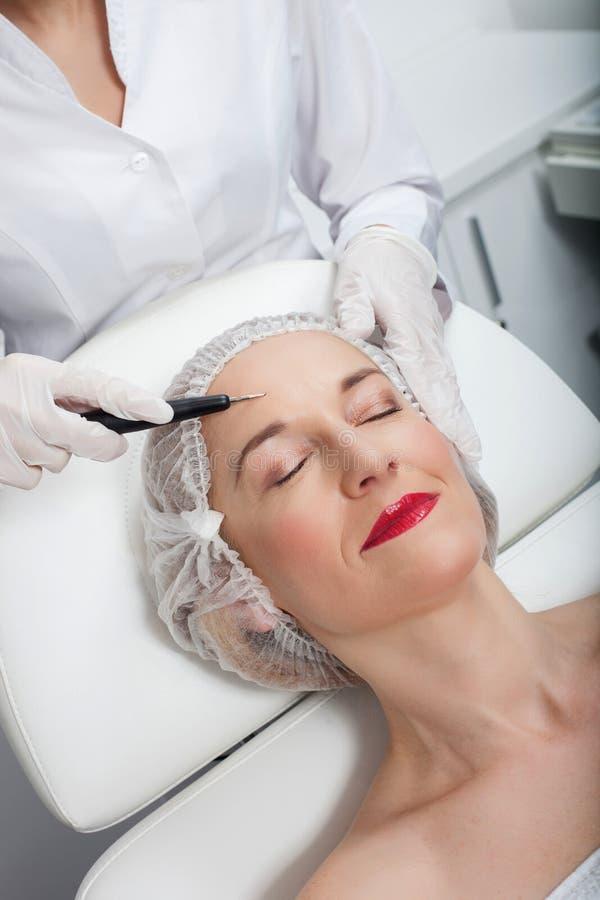 Nette ältere Dame besucht sachverständigen Kosmetiker lizenzfreies stockbild