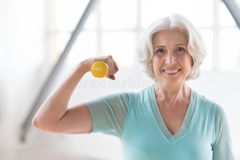 Nette ältere Frau, die an dem Training Freude hat stockfoto