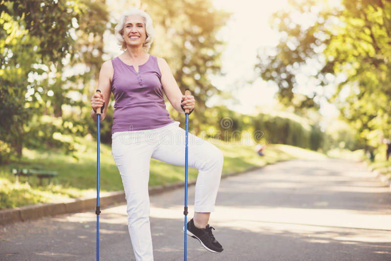 Nette ältere Frau, die eine körperliche Bewegung tut stockbild