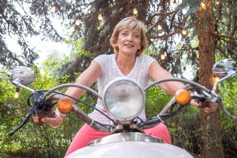 Nette ältere Frau, die einen Weinleseroller im Freien reitet stockfotografie