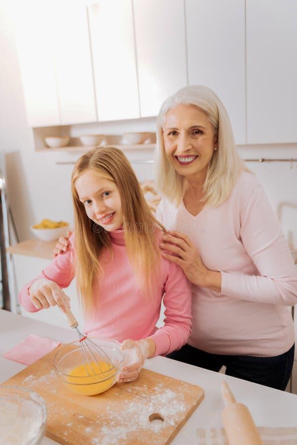 Nette ältere Frau, die ihre Enkelinschultern hält stockfotos