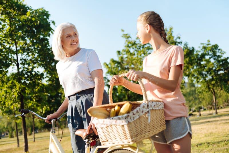 Nette ältere Frau, die zum Picknick mit ihrer Enkelin geht lizenzfreie stockbilder