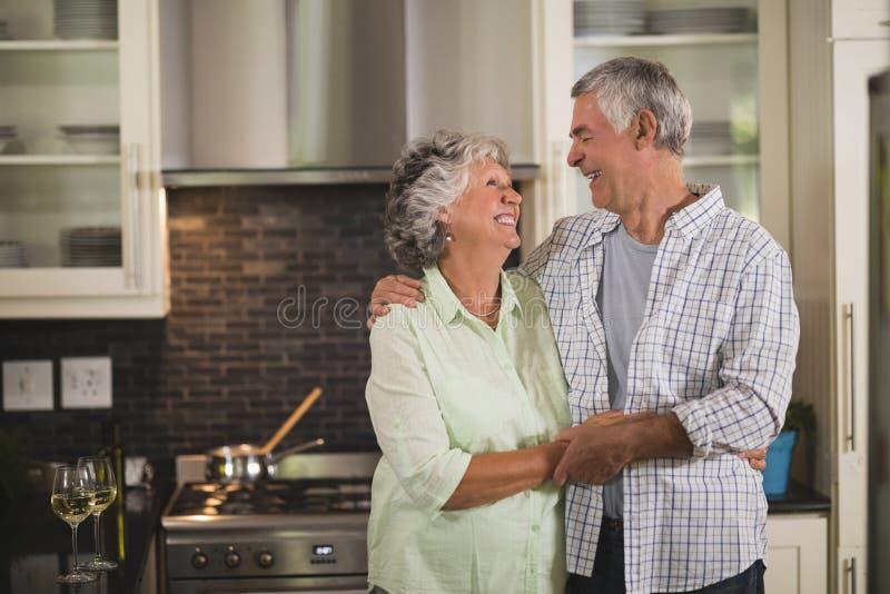 Nette ältere Paare, die in der Küche umfassen lizenzfreies stockfoto