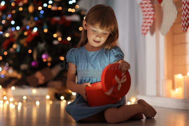 Nette Öffnungsgeschenkbox des kleinen Mädchens im Raum verziert für Weihnachten lizenzfreie stockfotografie