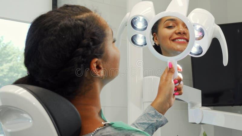 Nette Afrikanerin, die ihr gesundes Lächeln im Spiegel überprüfend lächelt lizenzfreie stockfotos