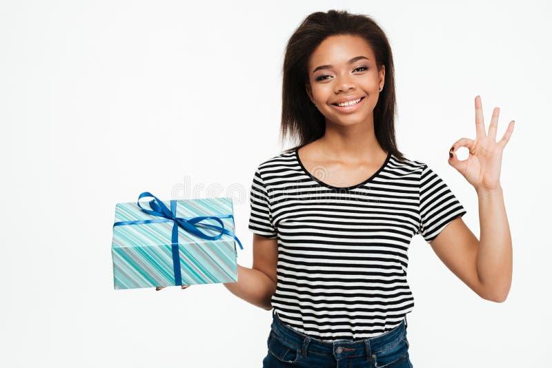 Nette afrikanische Frau, die Geschenkbox hält und okaygeste zeigt lizenzfreie stockbilder