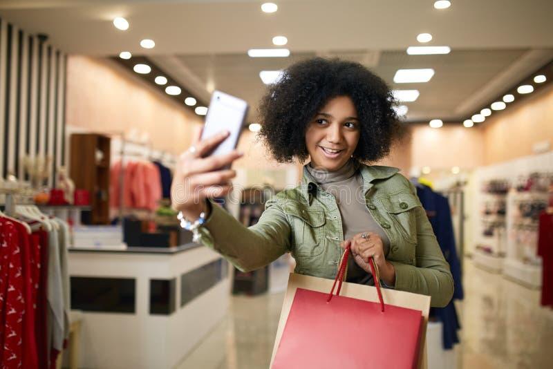 Nette Afroamerikanerfrau, die selfie mit Einkaufstaschen nimmt und nahe Bekleidungsgeschäft lächelt Schwarzes hübsches Mädchenneh stockfotos
