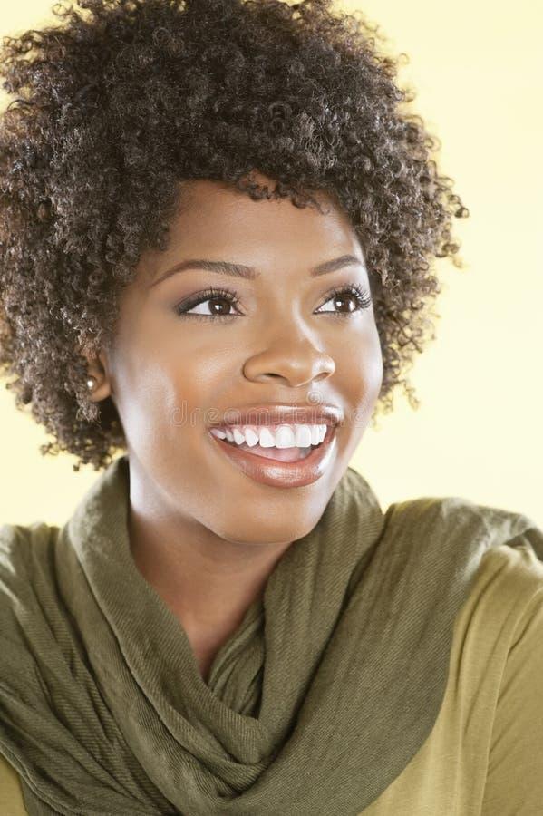 Nette Afroamerikanerfrau, die weg über farbigem Hintergrund schaut stockbilder