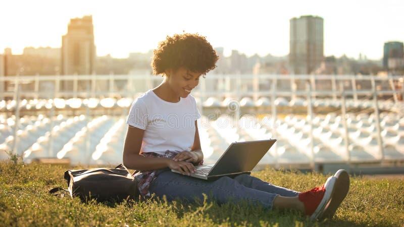 Nette Afroamerikanerstudentin, die drau?en auf Laptop-PC, freiberuflich t?tig schreibt lizenzfreie stockfotografie