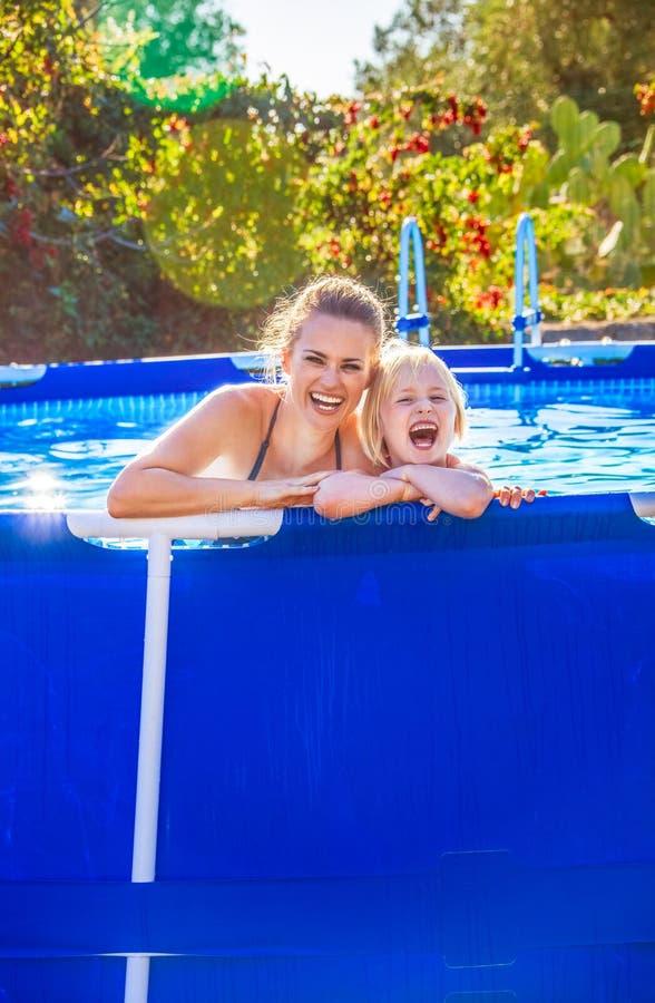 Nette aktive Mutter und Tochter im Swimmingpool lizenzfreie stockfotografie