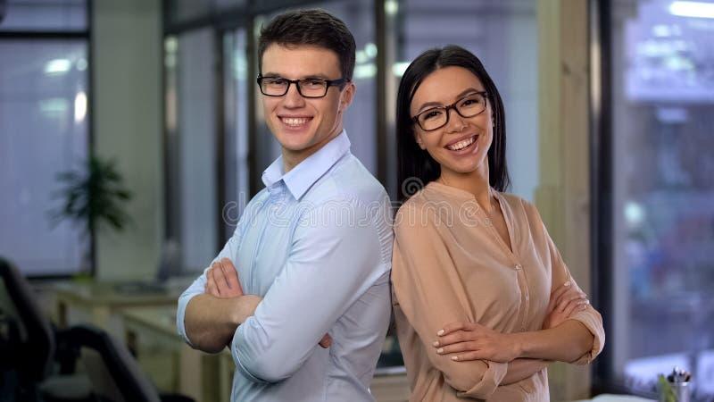 Nette Angestellte, die f?r Kamera, Arbeit f?r die jungen und Energieleute, Team aufwerfen lizenzfreie stockfotografie