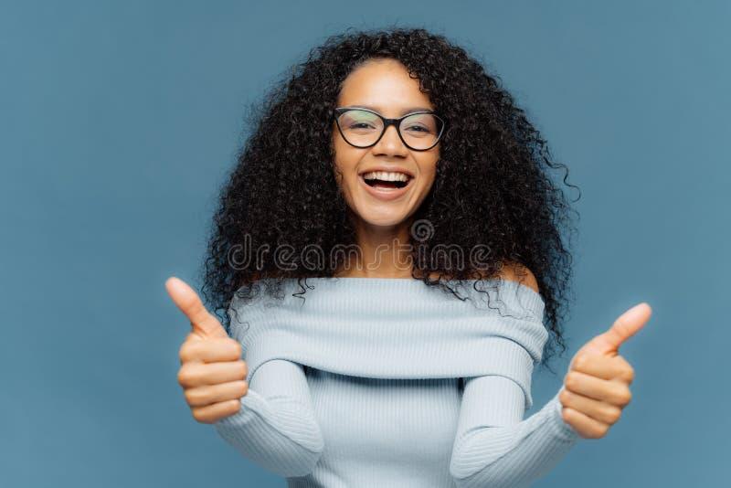 Nette Arbeit Freundliche glückliche Afroamerikanerfrau empfiehlt etwas und gibt Zustimmung, trägt optische Gläser und Pullover, lizenzfreies stockbild