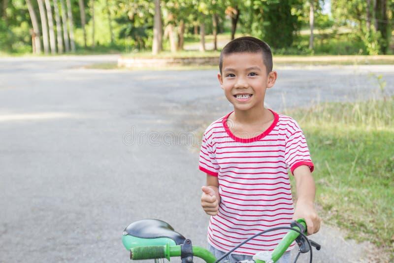 Nette asiatische Jungenfahrt ein Fahrrad in einem Park lizenzfreie stockfotografie