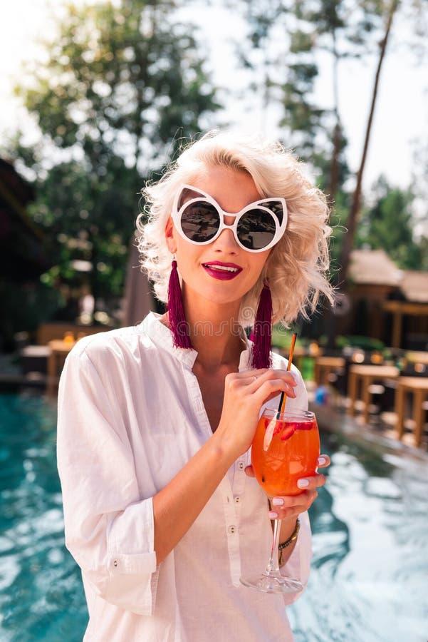 Nette attraktive Blondine, die ihr Cocktail trinken lizenzfreie stockbilder