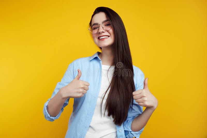 Nette attraktive Frau mit den Brillen, welche die Daumen oben lokalisiert auf dem gelben Hintergrund zeigen stockbilder