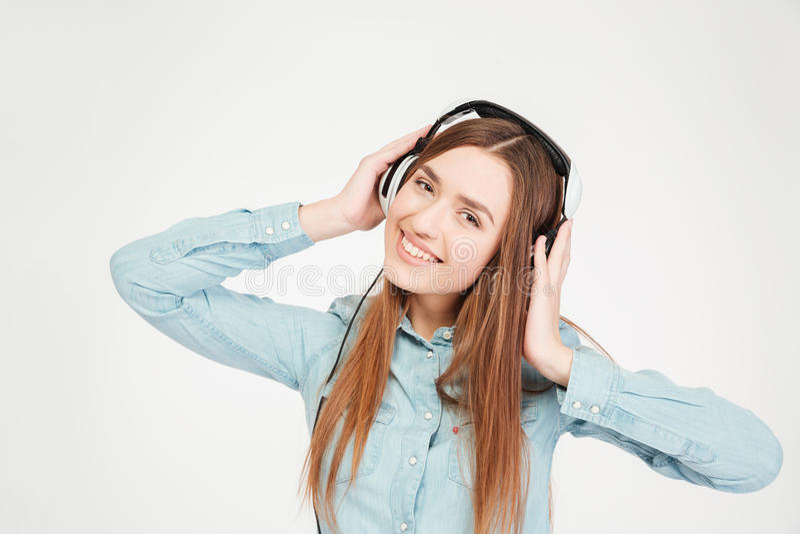 Nette attraktive junge Frau in den Kopfhörern hörend Musik stockfotografie