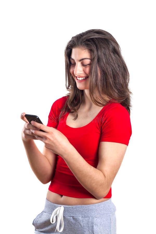 Nette attraktive junge Sportlerin, die Handy über wh verwendet stockfotos