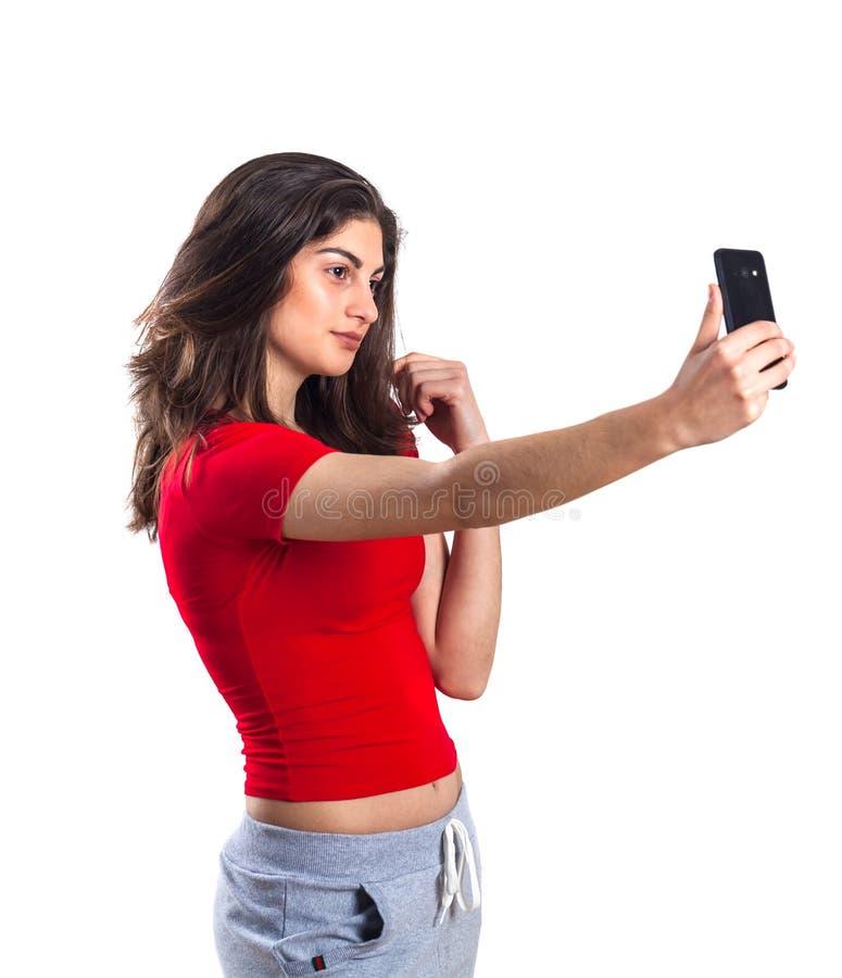 Nette attraktive junge Sportlerin, die Handy über wh verwendet lizenzfreie stockfotografie