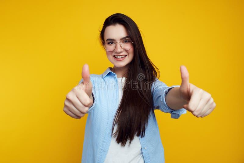 Nette attraktive weibliche darstellende Daumen oben lokalisiert auf der orange Wand lizenzfreie stockbilder