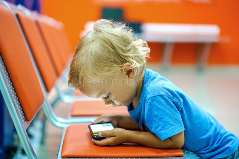 Nette aufpassende Karikaturen des kleinen Jungen auf Smartphone im Warteraum lizenzfreies stockfoto