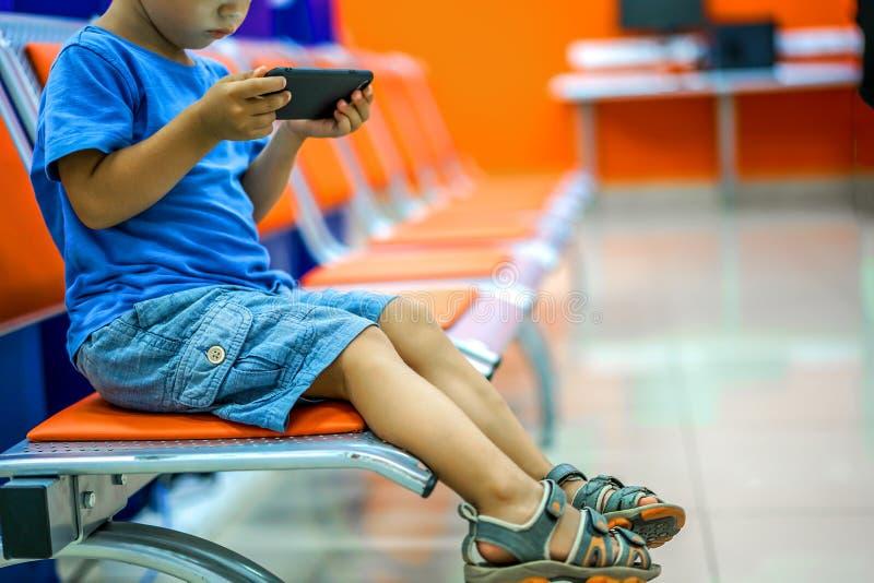 Nette aufpassende Karikaturen des kleinen Jungen auf Smartphone im Warteraum lizenzfreie stockfotos