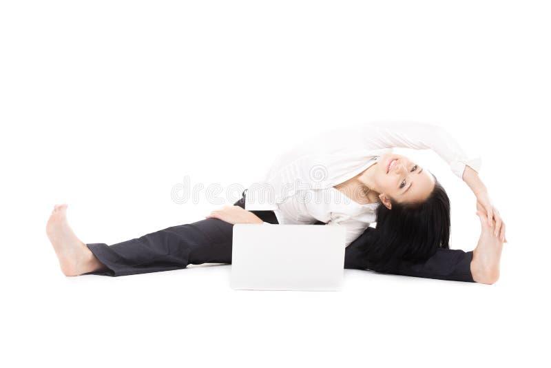 Nette Bürofrau mit dem Laptop, der Yogahaltung auf weißem backg tut stockfotos