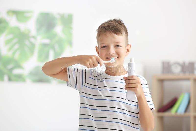 Nette bürstende Zähne des kleinen Jungen zu Hause stockfotos
