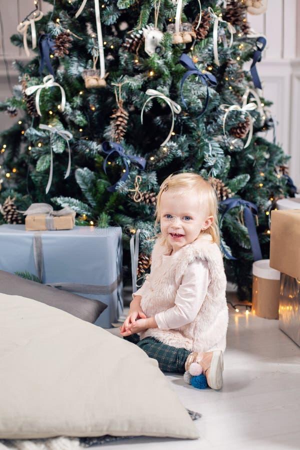 Nette Baby- und Weihnachtsgeschenke Kleines Kind, das Spaß nahe Weihnachtsbaum im Wohnzimmer hat Liebevolle Familie frohe Weihnac stockfotos