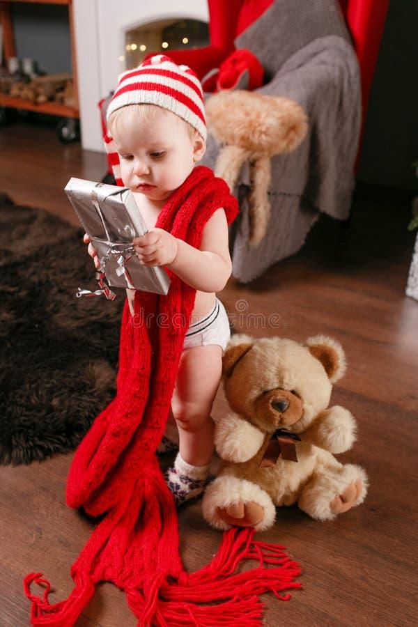 Nette Baby- und Weihnachtsgeschenke Kleines Kind, das Spaß nahe Weihnachtsbaum im Wohnzimmer hat Liebevoller Familiensohn fröhlic lizenzfreies stockbild