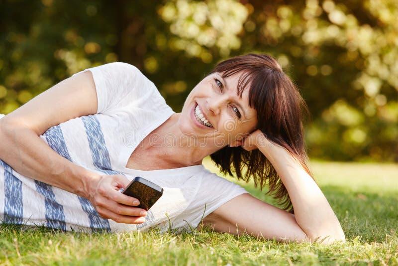 Nette bequeme Frau, die im Gras mit intelligentem Telefon liegt stockfoto