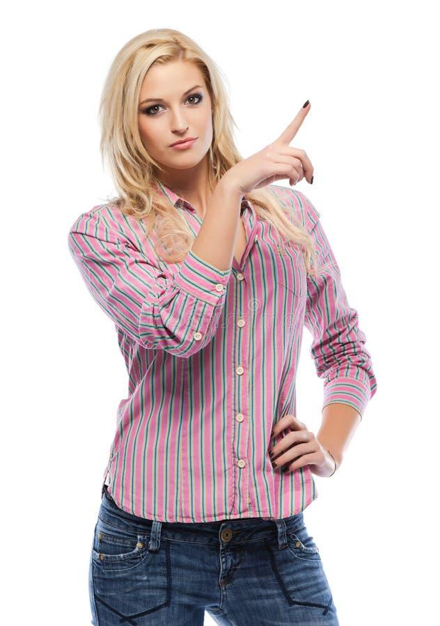 Nette blonde Frau, die auf copyspace zeigt lizenzfreies stockfoto