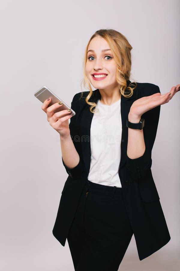 Nette blonde junge Bürofrau im weißen Hemd, schwarzer Anzug mit dem Telefon, welches die Kamera lokalisiert auf weißem Hintergrun lizenzfreie stockbilder