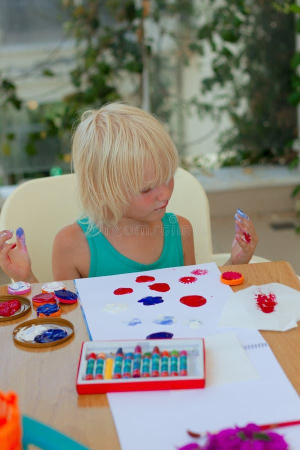 Nette blonde Kleinkindmädchenzeichnung mit Stempeln, Farben und Farbbleistiften lizenzfreie stockbilder