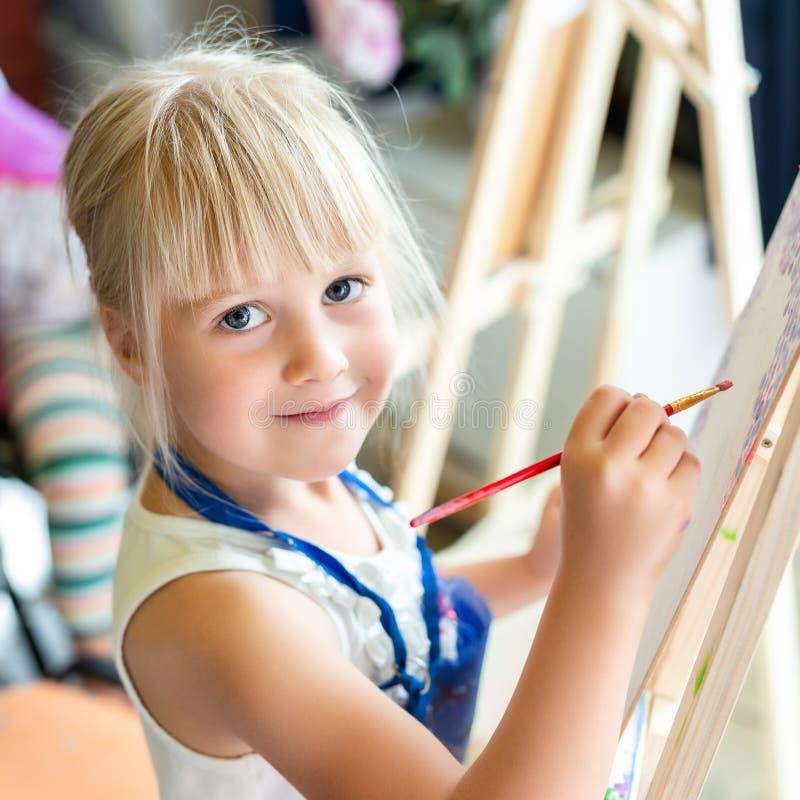 Nette blonde lächelnde Mädchenmalerei auf Gestell in der Werkstattlektion am Kunststudio Kinderholdingbürste in der Hand und Spaß stockfotografie