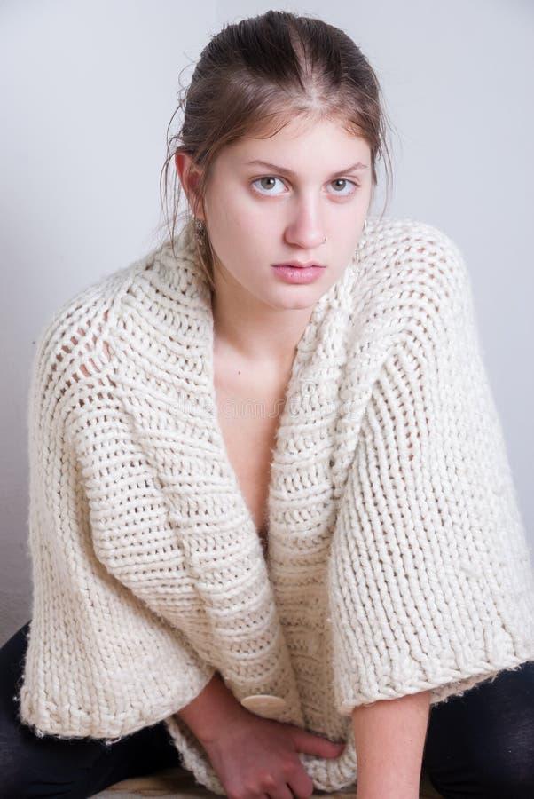 Nette Blondine, die gestrickten woolen Pullover trägt stockbild