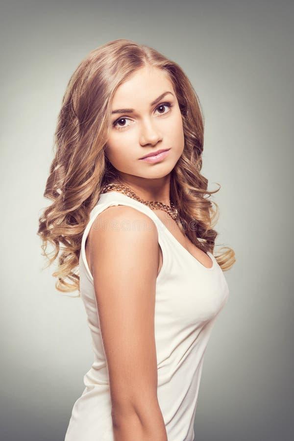 nette blondine mit braunen augen und den langen gelockten haaren